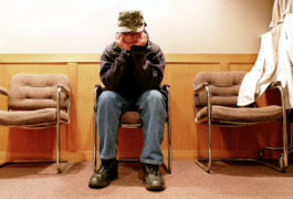 child sitting with face down outside principal's office