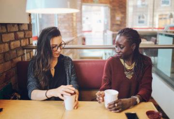 two women sitting in a coffee shop