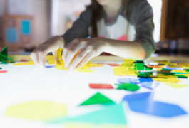 child working on colorful puzzle on lightbox