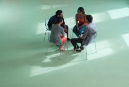 Birdseye view of four adults sitting in a circle talking
