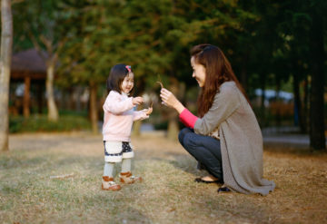 asian child and mother together in a park