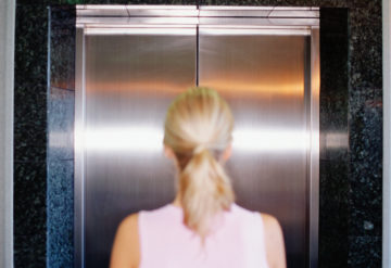 woman in front of closed elevator door