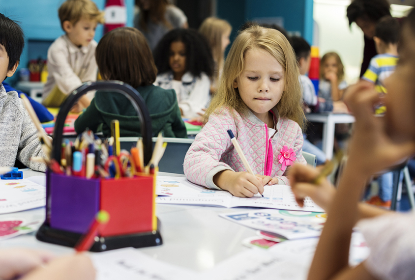 Child coloring in a classroom