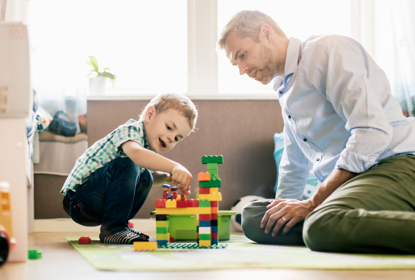 child and father playing with blocks at home