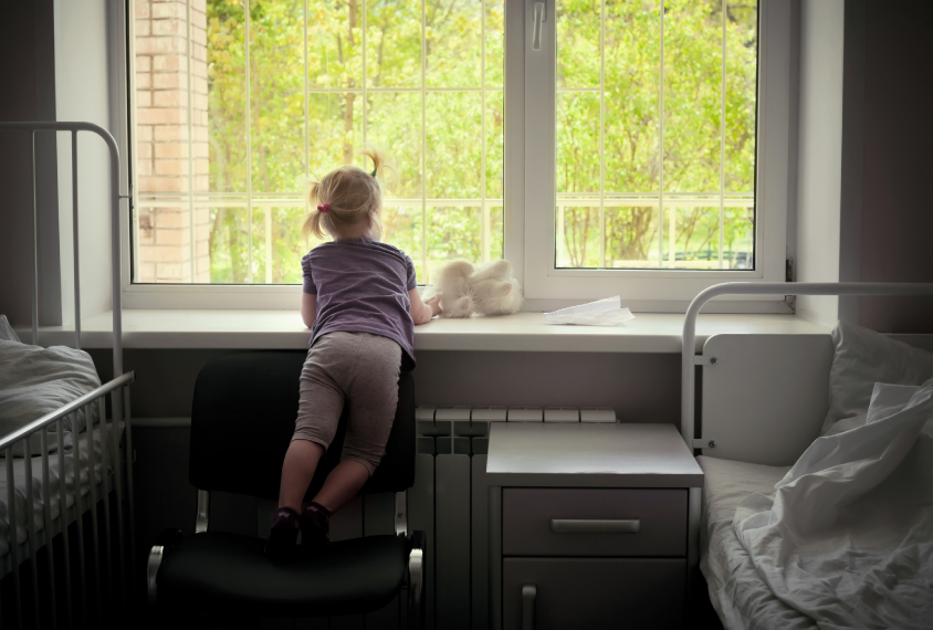 child looking out a hospital window