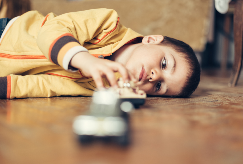 boy lying down on the floor touching a metal object