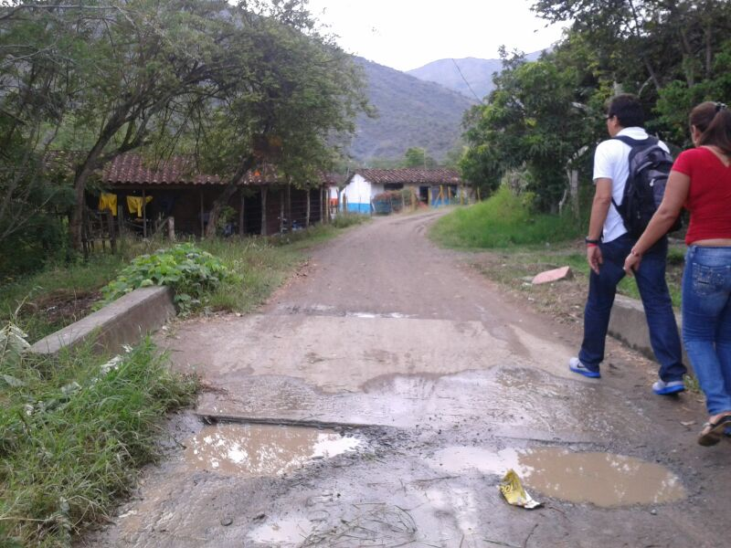 two people walking down dirt road in a town in colubmia