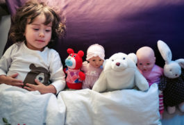 young girl sleeping with stuffed animals and dolls