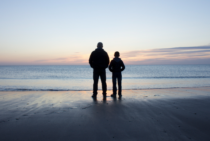 father and son standing on the beach during sunset