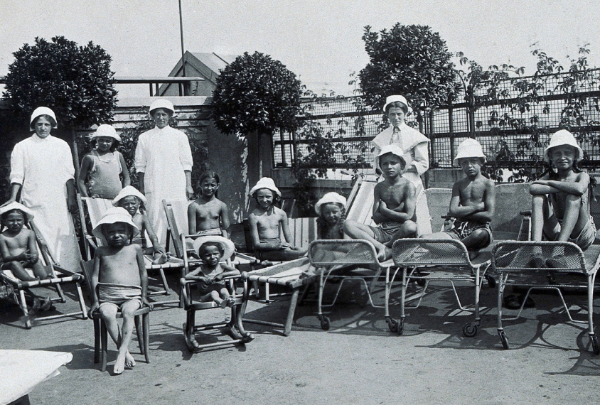 Vienna children's hospital, children in sun hats with attendants outdoors on chaise lounges and chairs.
