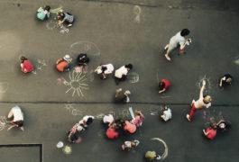 birdseye view of children drawing with chalk on the sidewalk
