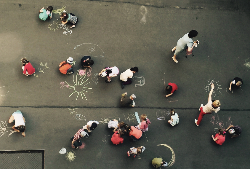birdseye view of children drawing with chalk on the sidewalk