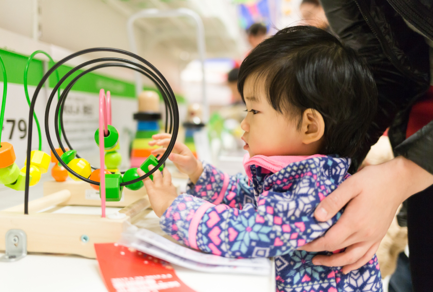 small toddler looks at colorful motor skills toy in store with mother