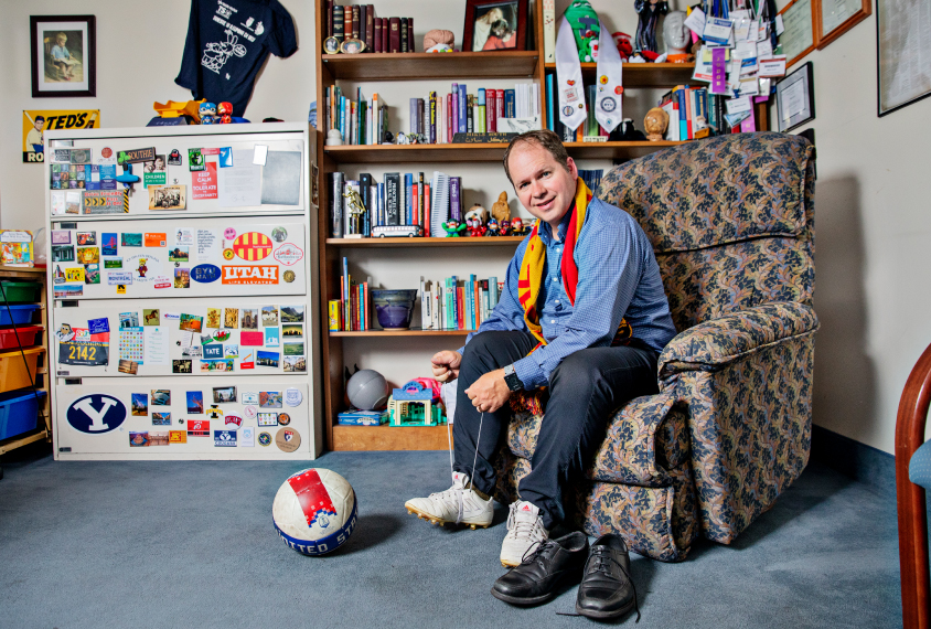 Mikle South laces up his soccer cleats in his colorful office