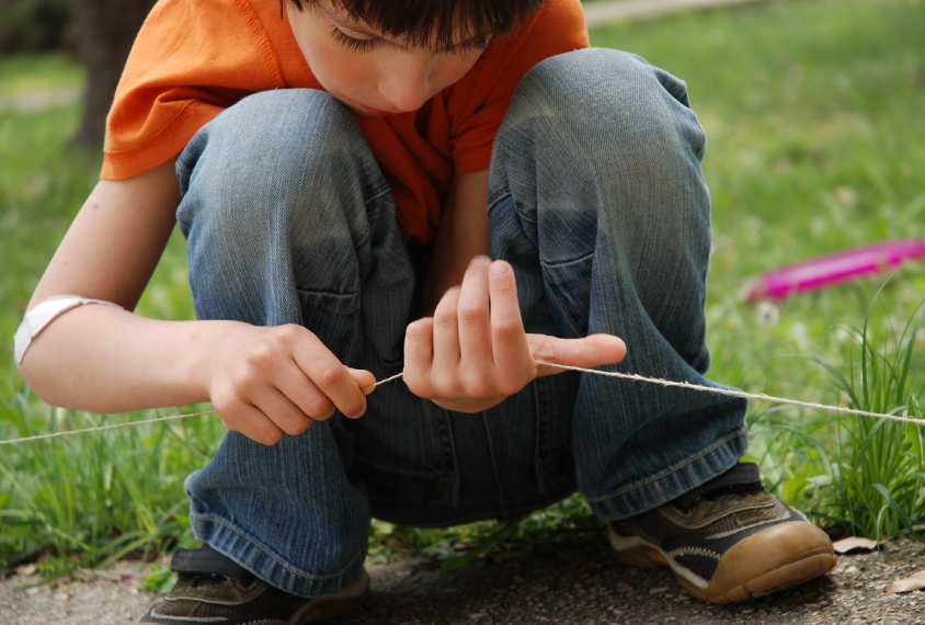 Boy examining string in the grass