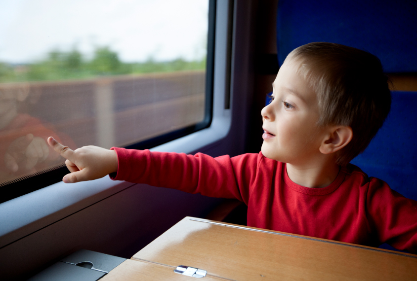 Boy pointing out moving train window
