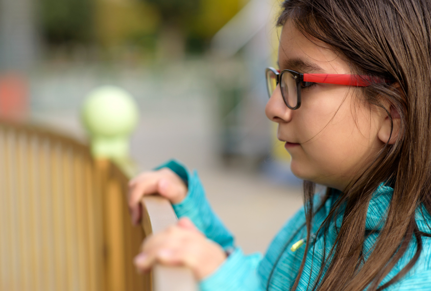 Elementary school age girl with glasses watches from outside a fence.