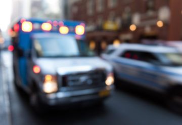 An ambulance and a police car on a city street, lights on.