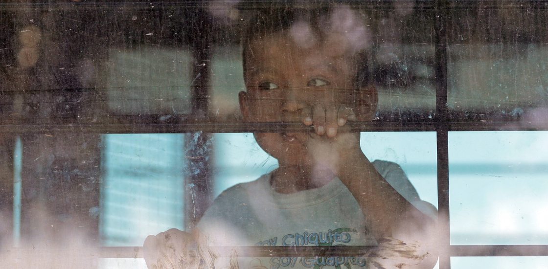 A lone child looks out from a U.S. Border Patrol bus leaving as protesters block the street outside the U.S. Border Patrol Central Processing Center Saturday, June 23, 2018, in McAllen, Texas.
