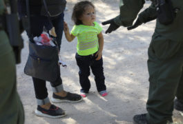 U.S. Border Patrol agents take Central American asylum seekers into custody on June 12, 2018 near McAllen, Texas. A child looks uncertainly at an agent wearing black gloves.