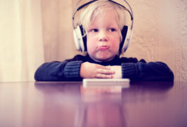 Little boy with headphones on sits at a table, making a funny face.