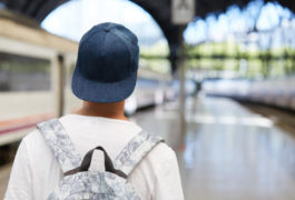 Boy in cap and backpack looks away from camera in train station.