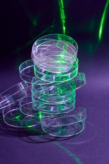 Empty petri dishes in a stack, with a green light shining on them.