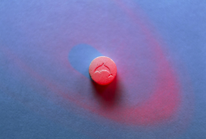A single ecstasy pill on a blue background.