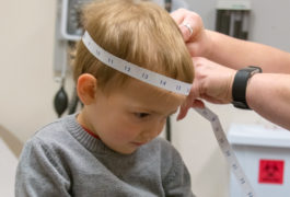 Toddle boy having his head measured in a medical setting.