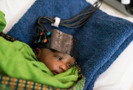 Infant in fnirs cap, wrapped in blankets.