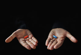 Two hands hold two pills, one red and one blue.