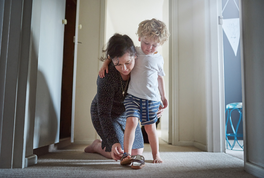 A woman helps her son put on his shoe.