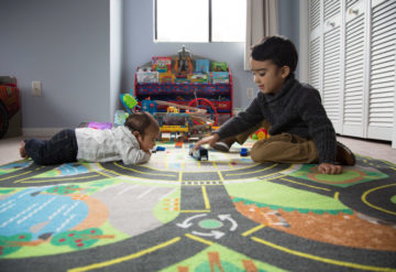 Siblings, a baby and a toddler, play together at home.