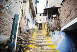 A man walks up a decrepit staircase in his neighborhood in Lima, Peru.