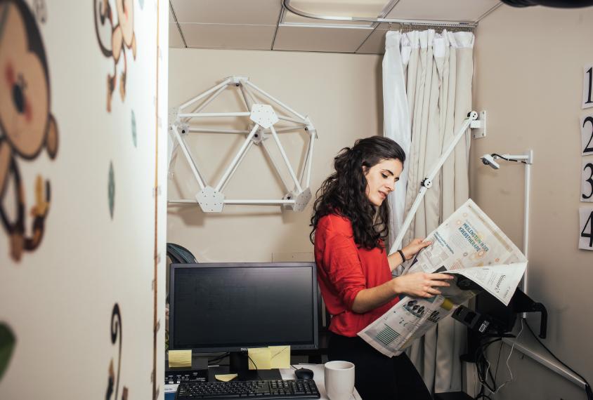 Gabriela Roseblau reading a German newspaper in her lab.