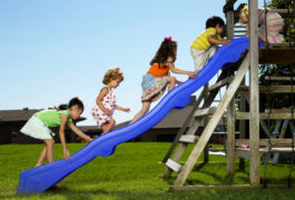 Group of young children climb up a blue slide outdoors on a sunny day.
