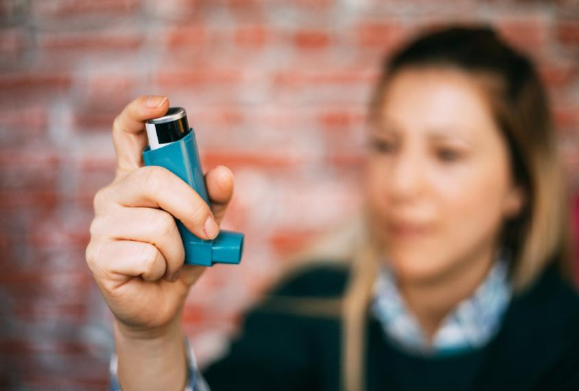 Woman holding inhaler.