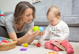 母亲给蹒跚学步的孩子提供玩具