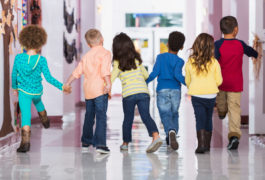 A group of boys and girls holding hands walking on a school hallway