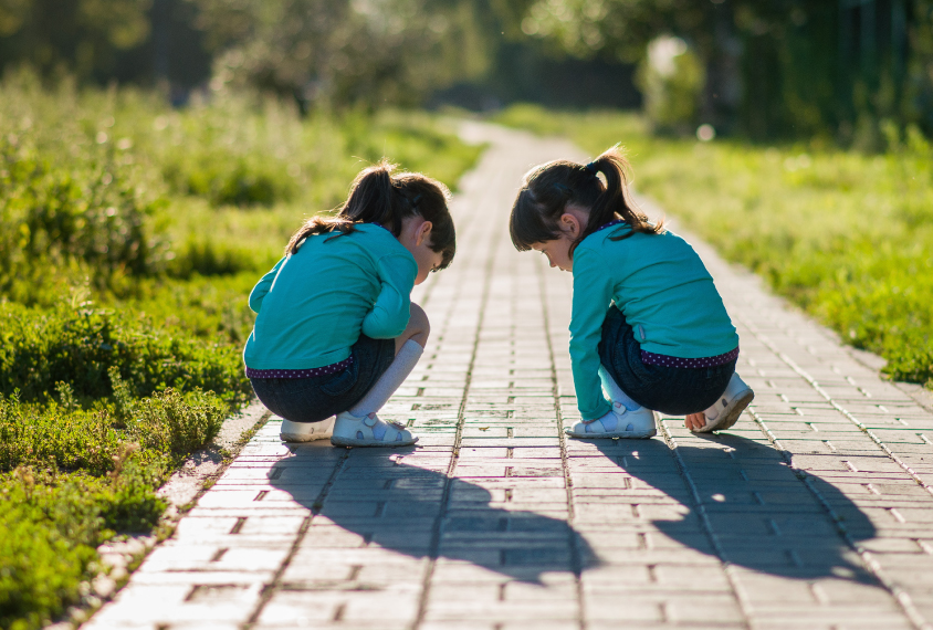 Two twin girls wearing blue kneeling down on the ground.
