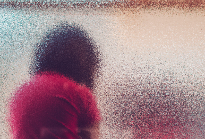 Child in sad posture, seen from through a textured glass window