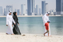Arab family walking on the autumn beach