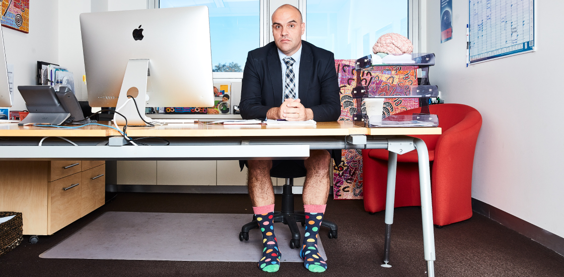 Goofy portrait of Adam Guastella at his desk in shorts and jacket with tie
