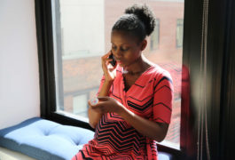Pregnant woman studies the label on medicine bottle while on the phone.