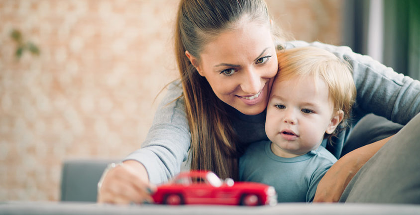 Mom and toddler looking at a red toy car