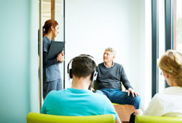 Adults in a waiting room, a man talks to a nurse or doctor in medical setting