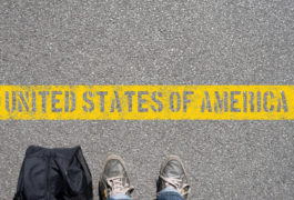 """feet in worn sneakers stop in front of a yellow line on the pavement that reads: """"United States of America"""""""