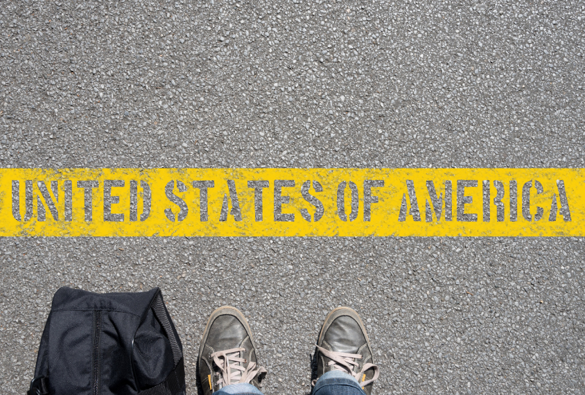 feet in worn sneakers stop in front of a yellow line on the pavement that reads: 'United States of America'