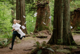 Scientist Annie Ciernia runs in the forest, wearing lab coat and carrying a stack of papers that are also flying along behind her