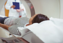 Woman inside MRI machine with clinicians or doctors looking on with clipboards